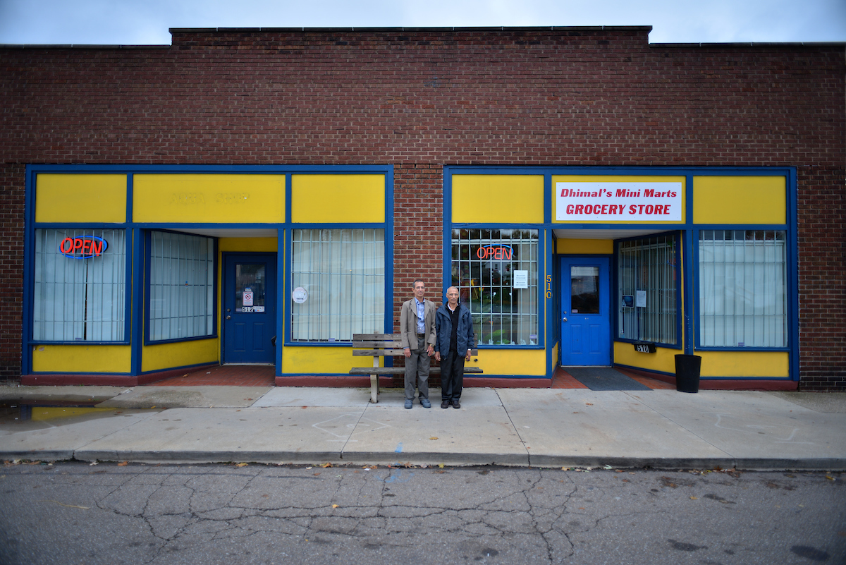The owners of Dhimal's Mini Marts stand outside the grocery store, which is located in North Hill.
