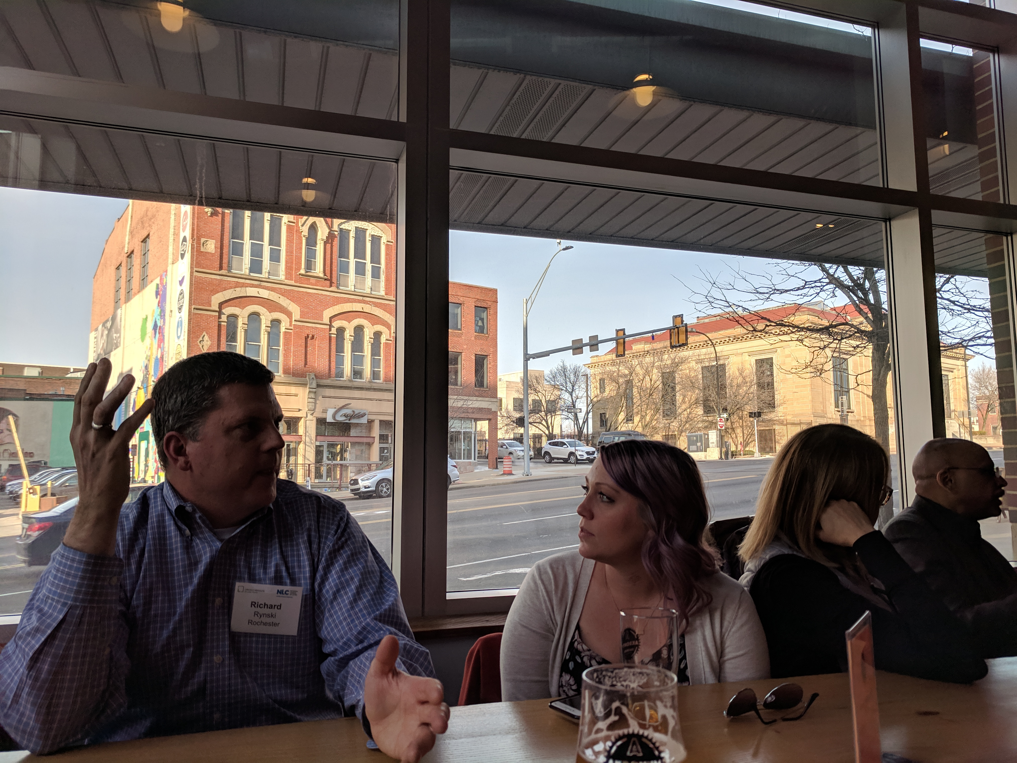 Two community of practice participants enageg in a discussion at a table at the Akronym Brewing Company.