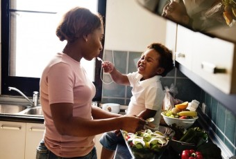 A woman feeds a toddler in a kitchen.