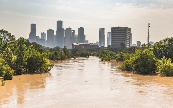 Agua de inundación marrón con la ciudad de Houston en el fondo