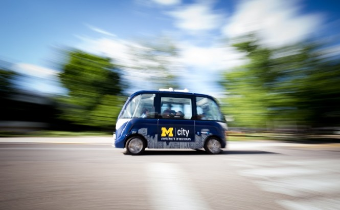 This image shows a street with a blue driverless shuttle in the middle. Blurred trees sit in the background of the image.