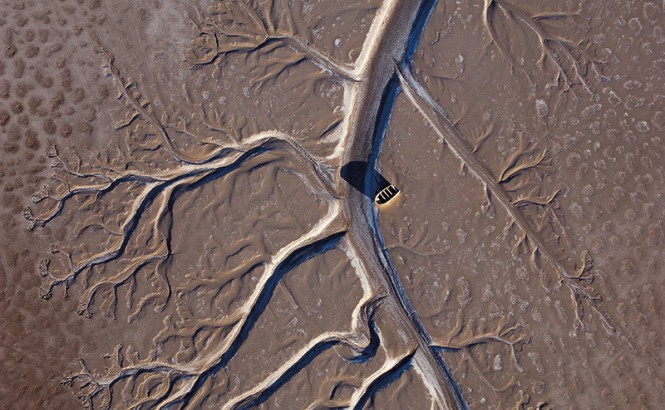 Aerial view of a fishing boat stranded on a brown and dried up Colorado River Delta.