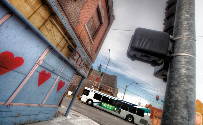 Photograph shows the side of a blighted building on a city street with crumbling paint, graffiti, and a broken store sign. A new bus drives down the street nearby. Credit: Eric Bowers.