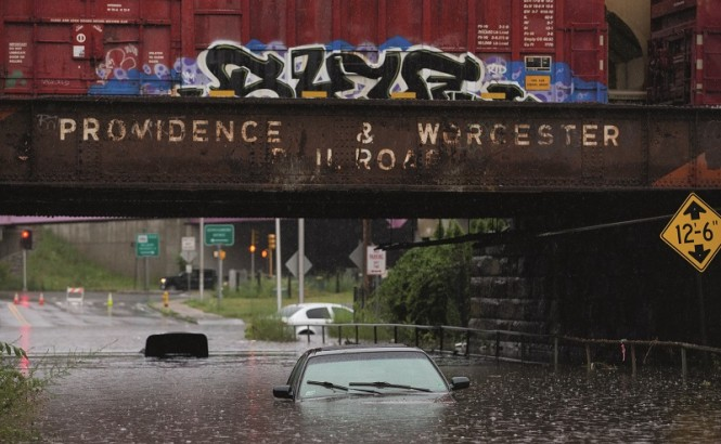 A car sits submerged under water as a results of heavy flooding. The car sits under an aging Providence & Worcester Railroad bridge in Worcester.