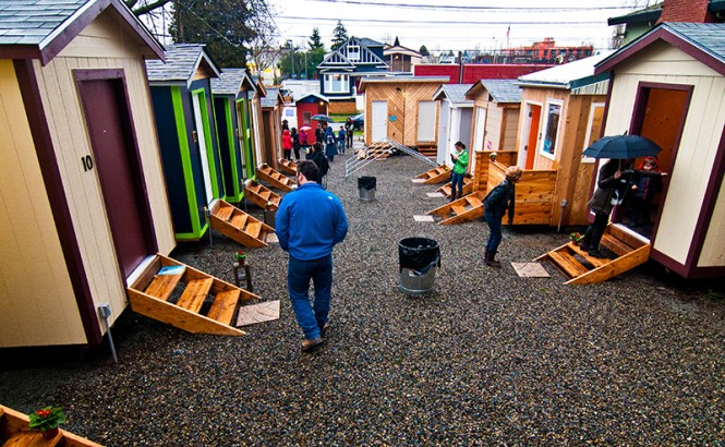 A man wearing a blue jacket and jeans walks along a paved or graveled pedestrian way, with several tiny homes on either side of the way. The homes are one-story tall and not much wider than their front doors and the roofs are peaked in the middle. Other people are seen walking further down the way and entering and exiting the homes. Credit: Low Income Housing Institute