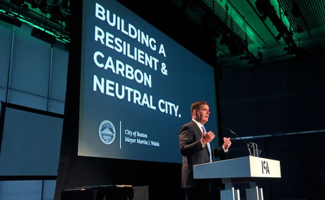 Boston Mayor Martin Walsh stands against the backdrop of a powerpoint presentation at a podium speaking to a crowd at the annual Greenovate Awards.