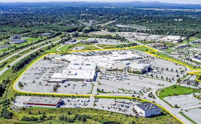 Photograph shows an aerial view of a landscape with sky and blue mountains in the distance, and a large, low, spread out building surrounded by parking spaces. Retail stores around the building and parking lot give way to suburban and rural land with many dark green trees.