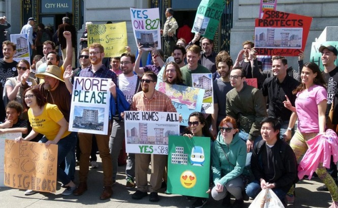 A group of YIMBY advocates pose for a picture with signs supporting California bill SB 827.
