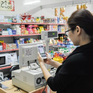A woman scans a QR code that is taped to a cash register in a grocery store in Beijing