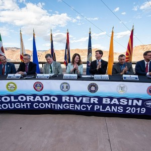 Federal and state officialssit at a table to celebrate the signing of theColorado Riverdroughtcontingencyplan atop the Hoover Dam
