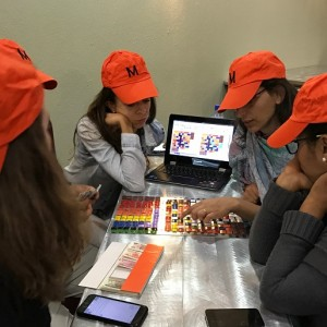 """A group of participants in a Lincoln Institute course wear orange hats and gather around a game board. The hats say """"M"""" for """"middle class."""""""