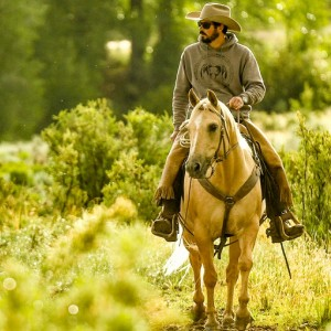 Colorado rancher Paul Bruchez rides a horse in a green field.
