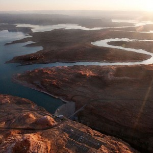 The sun glares white in the top right corner over a landscape of river and desert viewed from above. Two main branches of the Colorado river appear silver as they wind across the land and reflect the sun. They merge with the irregular, dark blue lake formed by a dam near the bottom center of the image. Roads also cross the landscape and run over the river near the dam. The terrain is a reddish brown, darker where it is in shadow.