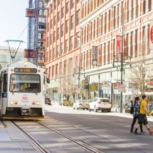Downtown Denver, Colorado. Shown are a light rail train and a few pedestrians crossing the street.