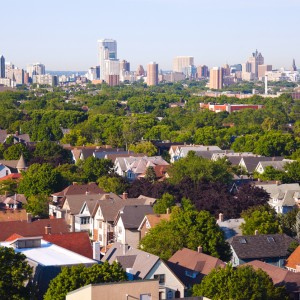 An aerial photo of houses and trees with an urban skyline in the background