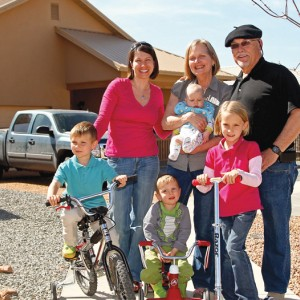 A family consisting of an older woman, older man, woman in her middle years, and four young children stands in front of a beige one-story home with a peaked roof. The older woman holds a baby and the other children are on bicycles and a scooter. There is a truck in the gravel driveway behind them.