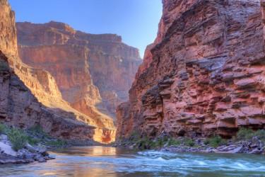 A river runs throuh a deep canyon made of reddish rock.