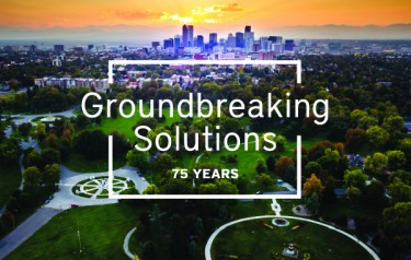 A park is in the foreground and tall buildings are visible furher out on the horizon. Text, overlaid on the photo, reads, groundbreaking solutions, 75 years.