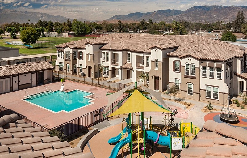 This image shows a playground, pool, and houses that are part of the Arrowhead Grove Neighborhood Revitalization Plan. Mountains and green space are visible in the background.