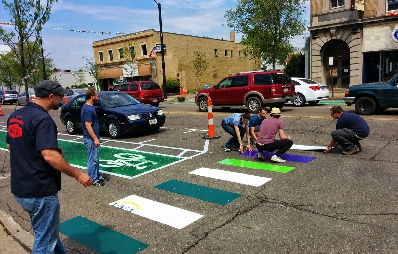 This picture shows several people laying down a new colorful crosswalk on a paved road.