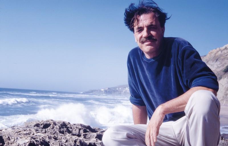 Un hombre, Ian McHarg, con bigote y cabello oscuro, vestido con un suéter azul y pantalones de colores claros mira a la cámara, en cuclillas en una playa rocosa. El cielo azul y las olas del océano están detrás de él.