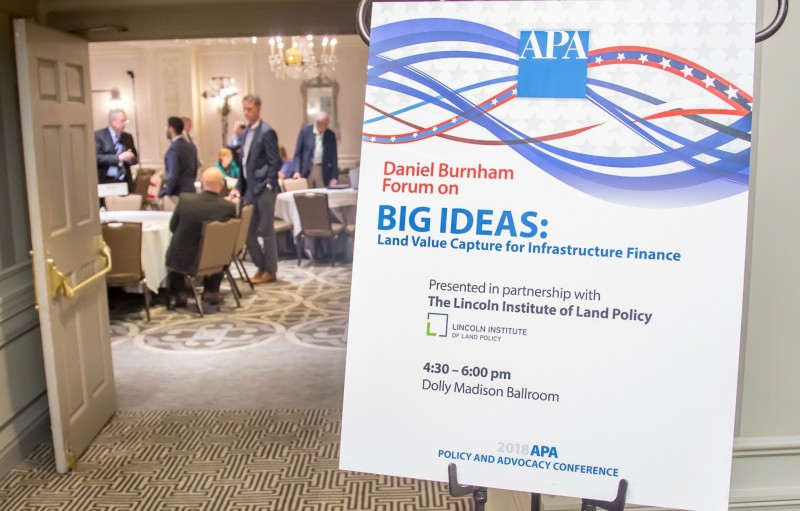 A placard occupies the right side of the frame. It reads Daniel Burnham Forum on Big Ideas: Land Value Capture for Infrastructure Finance. On the left side, people are milling around inside a room, viewed from a distance through a doorway.