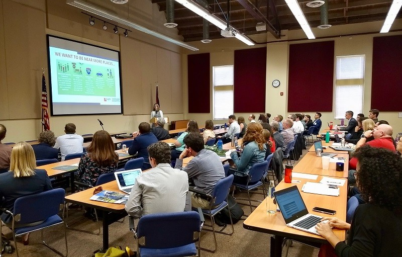 40 conference participants sit at desks looking at a power point presentation during the second annual Consortium for Scenario Planning Conference.