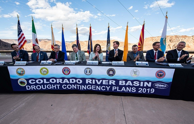 Federal and state officials sit at a table to celebrate the signing of the Colorado River drought contingency plan atop the Hoover Dam