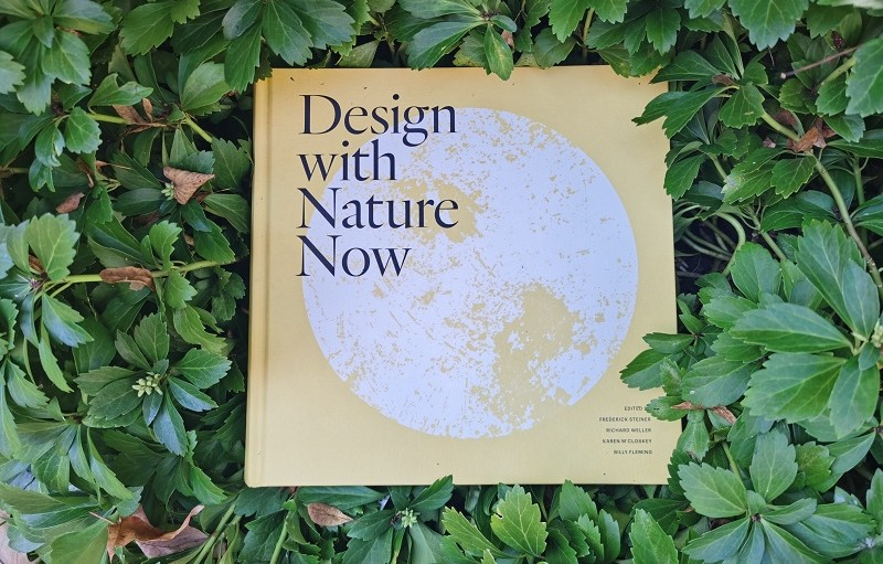 An image of the book Design with Nature Now surrounded by leaves.