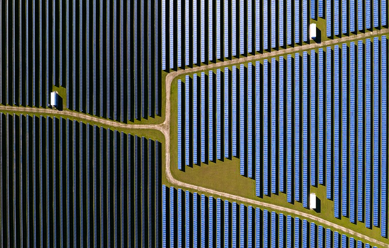 Dark blue vertical lines of solar panels seen from directly above fill a little more than a third of the left side of the image, while middle blue vertical lines of solar panels fill the remainder. A dirt road with green between it and the panels crosses the image from the left and branches into two roads in the middle and cross at angles to the top right and bottom right.