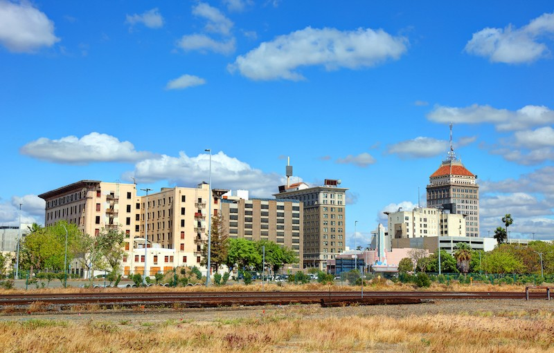 Dry grass in the foreground, train tracks mid-frame, and mid-rise buildings in the background with a blue sky behind them.