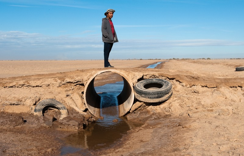 Against a blue sky with thin clouds, a male member of the Cocopah Tribe, wearing a hat, red t-shirt, dark sweater, and black pants, stands on a dirt road that sits atop a large irrigation pipe. The rest of the scene consists of an arid, brown landscape and a small stream of water that leads to the pipe, passes through it, and exits out the other side. Old tractor or car tires are placed against the dirt at either side of the pipe, and a third is seen in the distance.