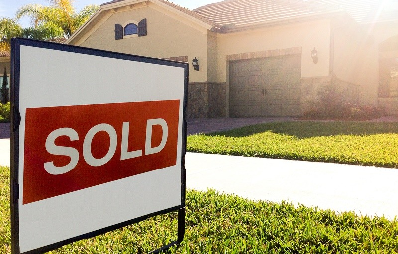 """A """"sold"""" sign sits on a front lawn in front of a large home."""