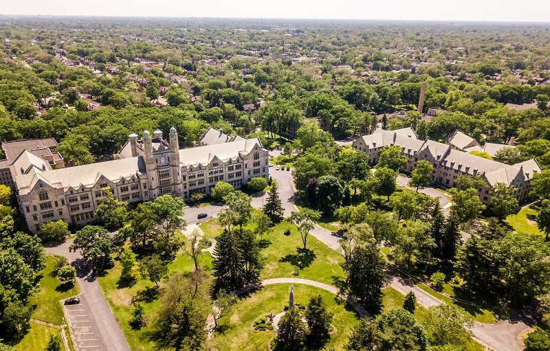 An aerial view of the Marygrove College campus and surrounding neighborhood. The campus and neighborhood have many trees. The two most visible buildings on the campus are old, large, and made of light stone with many lead paned windows. One of the buildings has a clock tower.