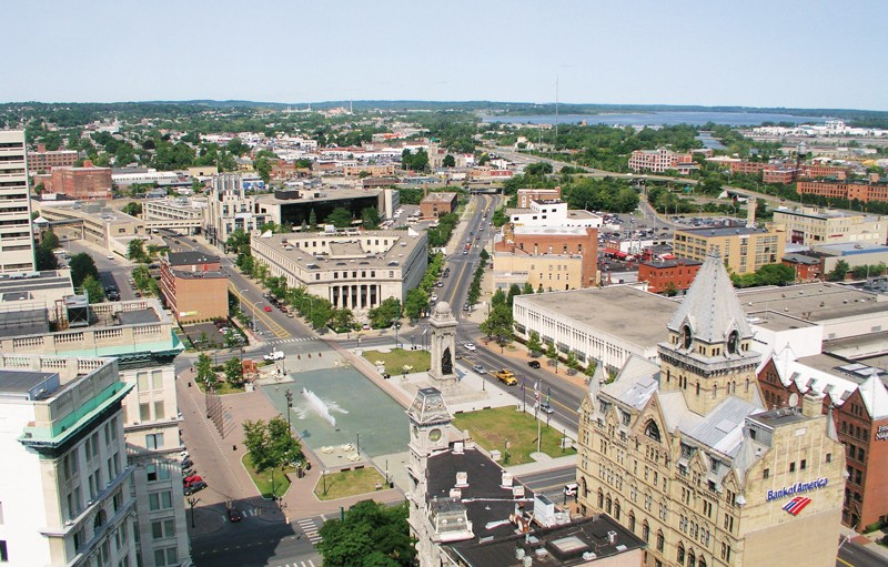Aerial view of Syracuse showing a municipal park and buildings, with and elevated section of Interstate 81 in the distance