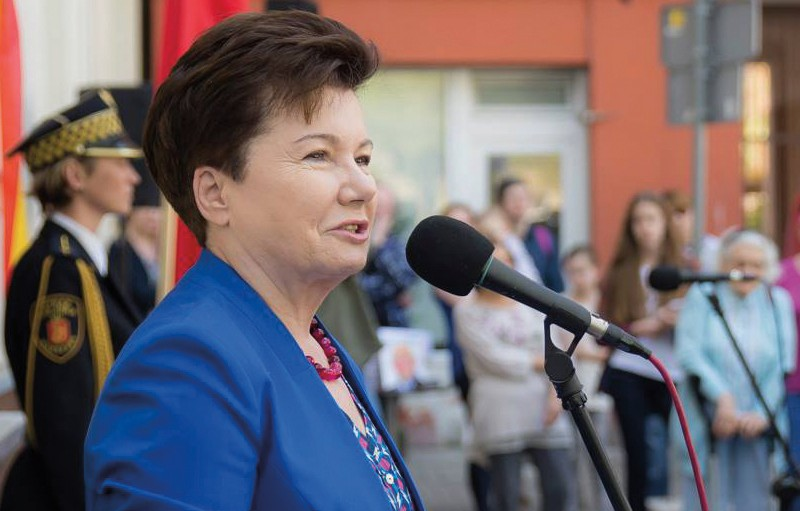 Photograph shows a woman, Mayor Hanna Gronkiewicz-Waltz, with short dark hair in profile while she speaks at a microphone. She wears a blue suit jacket with a red necklace and her expression is pleasant as she talks. There is an officer wearing a dress uniform in the background standing at ease, as well as several members of the public. Credit: City of Warsaw/Ewelina Lach.
