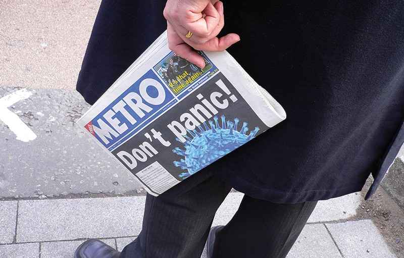 "Photograph shows a man from the middle down, standing on a sidewalk, wearing a dark coat and pants, and holding a Metro newspaper in one hand. The headline on the newspaper is ""Don't panic!"""