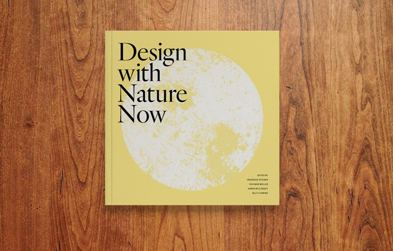 """A book is shown from above, lying flat on a wood table. The book is pale yellow with black type that reads """"Design with Nature Now"""" and also shows a white, moon-like image that takes up most of the cover."""