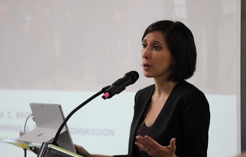 Sara Bronin speaks into a microphone. The background shows her power point presentation.