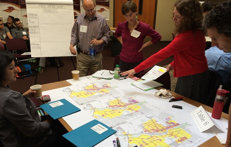 A group of planners stands over a map.