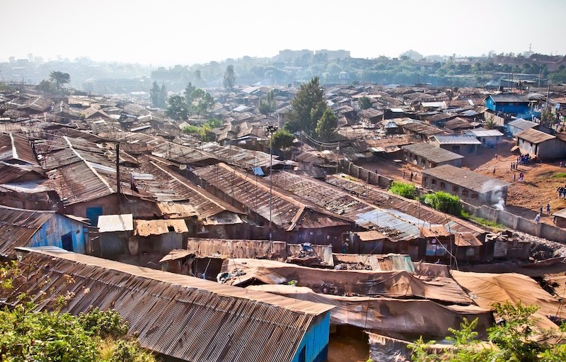 Shacks with corregated metal roofs are crowded together in most of the foreground, with a hazy urban skyline visible in the background.