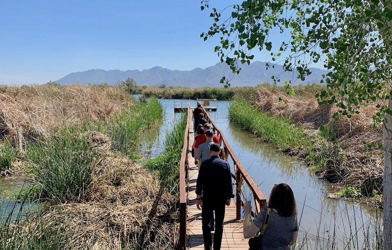 Several people are walking away from the camera on an elevated wooden walkway with a river in the foreground and mountains in the distance.