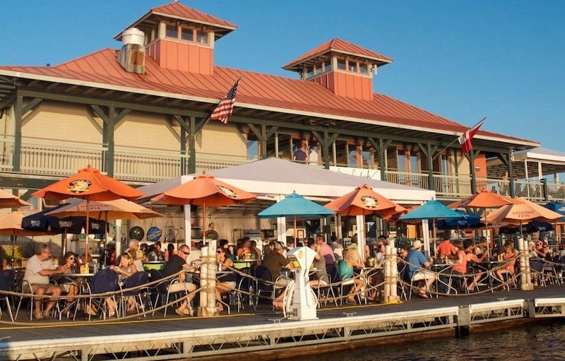 A waterfront restaurant with an outdoor patio full of diners.