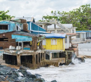 Photograph shows small turquoise, yellow, and white buildings situated directly over water on a coastline in Rincón, Puerto Rico. Rough waters are visible. Rincón sustained heavy damage in Hurricane Maria. Credit: cestes001 (iStock/Getty Images Plus)