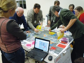 Photograph of several people standing around a table on which there is a colorful plan showing streets and buildings. Some of the people lean toward the surface of the table to place colored stickers on the plan. A laptop computer on the table shows another version of the plan.